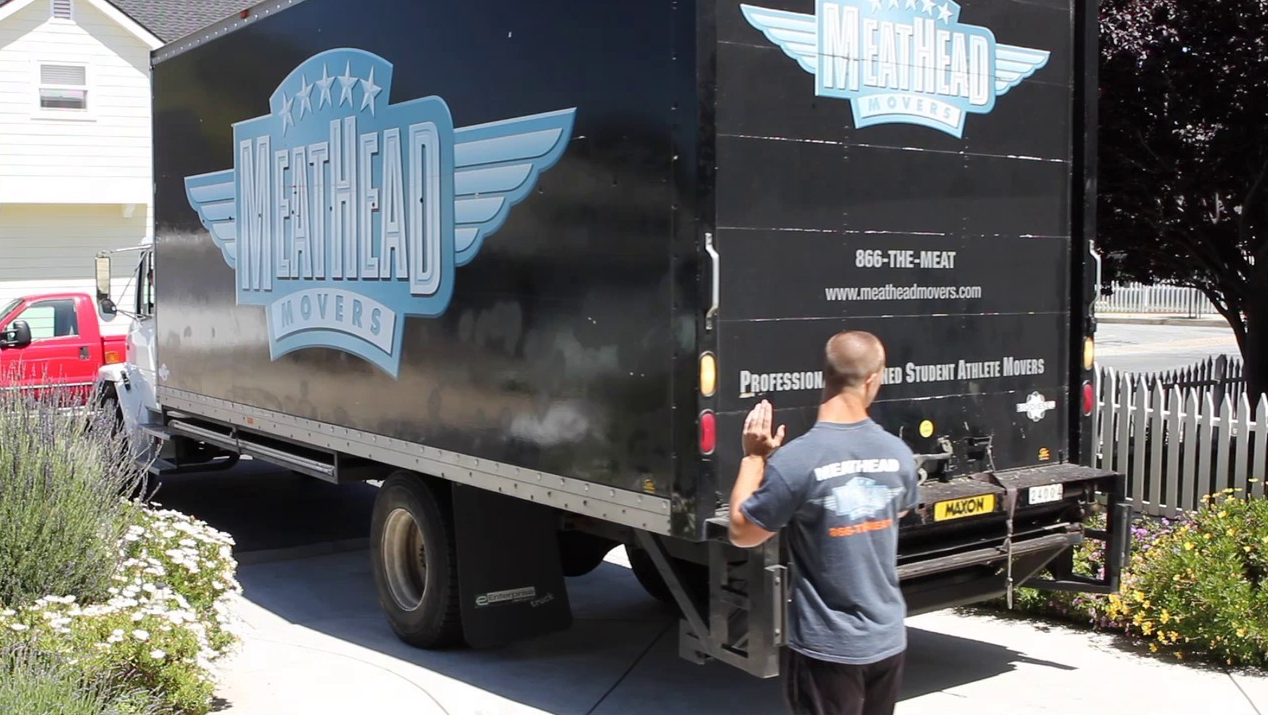 A Meathead Movers employee directs a moving truck. The company practices social entrepreneurship on a local level.